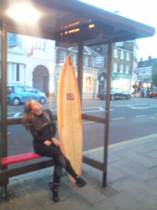 girl with surfboard by bus stop